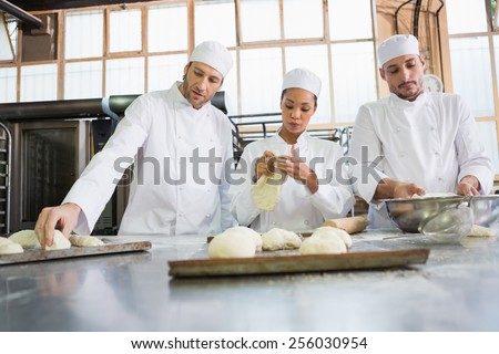 Concentrated colleagues kneading uncooked dough in the kitchen of the bakery - stock photo