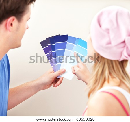 Concentrated couple choosing color for a room in their new house