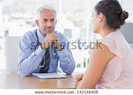 Concentrated doctor listening to patient in his office - stock photo