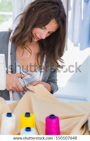 Concentrated fashion designer cutting textile - stock photo