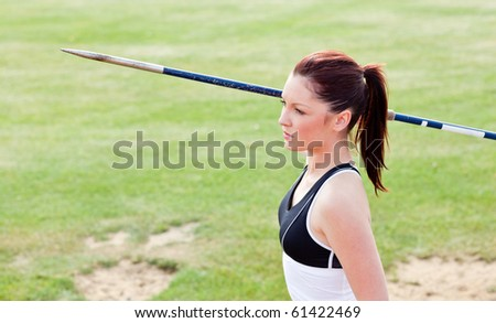 Concentrated female athlete ready to throw javelin in a stadium - stock photo