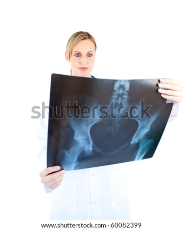 Concentrated female doctor looking at a x-ray against a white background