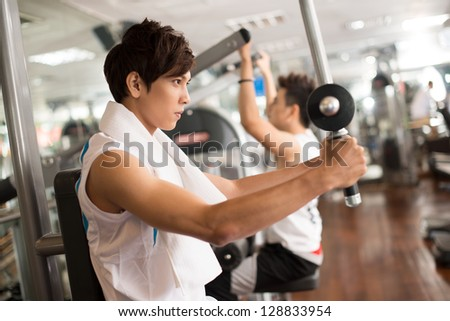 Concentrated guys building muscles in a gym