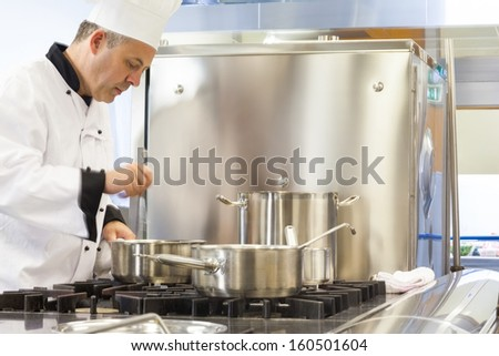 Concentrated head chef stirring in pot in professional kitchen - stock photo