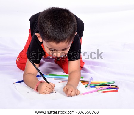 Concentrated little boy drawing  on paper with crayon. - stock photo