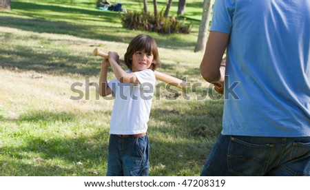 Concentrated little boy playing baseball with his father in the park - stock photo