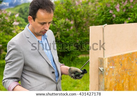 Concentrated male artist standing in front of his sketchbook wearing a glove and painting in a park with a background of beautiful bushes - stock photo