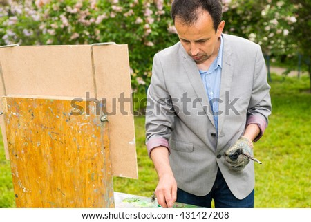 Concentrated male middle-agedpainter standing in front of his sketchbook wearing a glove and painting in a garden with a background of beautiful bushes - stock photo