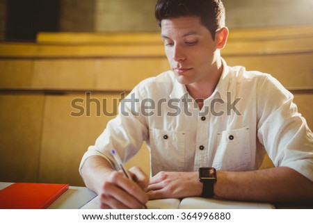 Concentrated male student during class in lecture hall - stock photo