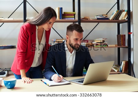 concentrated man and woman looking at laptop in office - stock photo