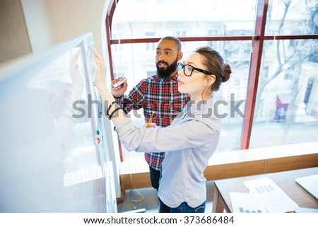 Concentrated man and woman students standing and writing on whiteboard in classroom  - stock photo