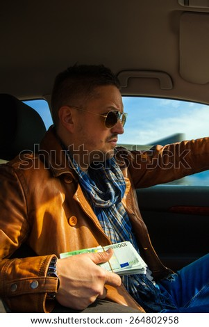 concentrated man in sunglasses with bundle of money in hands driven car. Inside photo - stock photo
