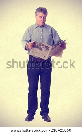 Concentrated man reading a newspaper - stock photo