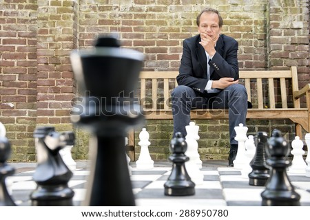 Concentrated man, thinking strategically about his next move, sitting on a wooden bench in front of a brick wall during an outdoor chess game using life sized chess pieces and chess board - stock photo