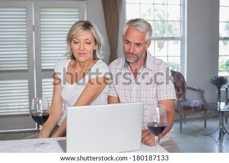 Concentrated mature couple with wine glasses using laptop at home