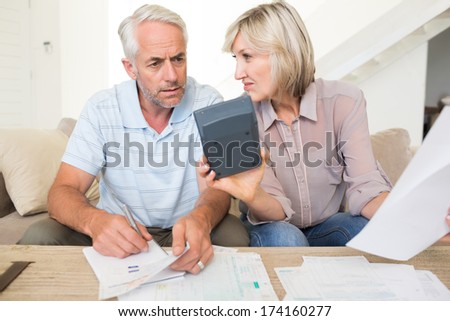 Concentrated mature man and woman with bills and calculator sitting on sofa at home