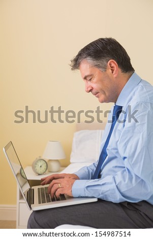 Concentrated mature man using a laptop sitting on a bed in a bedroom