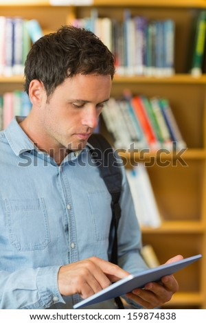 Concentrated mature student using tablet PC against bookshelf in the library