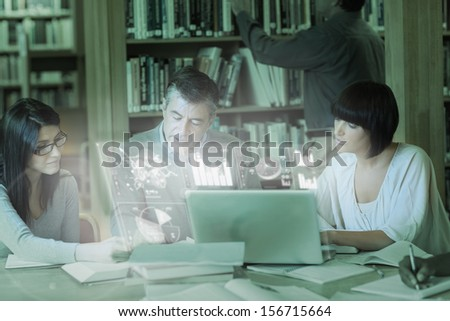 Concentrated mature students working together on digital interface in university library - stock photo