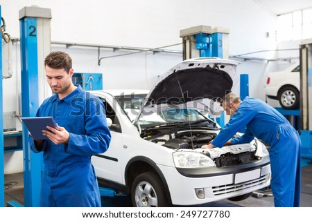Concentrated mechanic writing on clipboard at the repair garage - stock photo