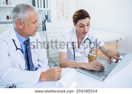 Concentrated medical colleagues discussing and pointing on laptop screen in the hospital - stock photo
