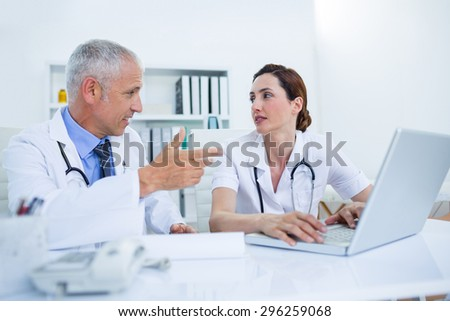 Concentrated medical colleagues discussing and working with laptop in the hospital - stock photo