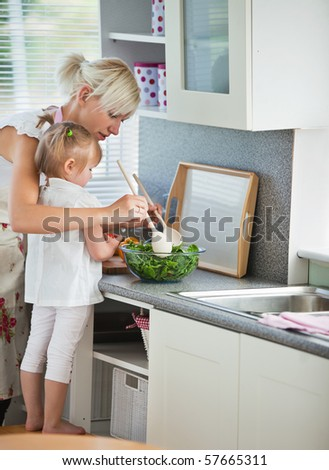 Concentrated mother and child cooking in kitchen - stock photo