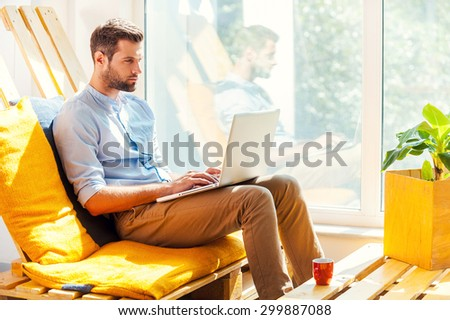 Concentrated on his work. Side view of concentrated young man working on laptop while sitting in the rest area of the office - stock photo