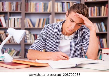 Concentrated on studying. Confident young man making research while sitting in library - stock photo