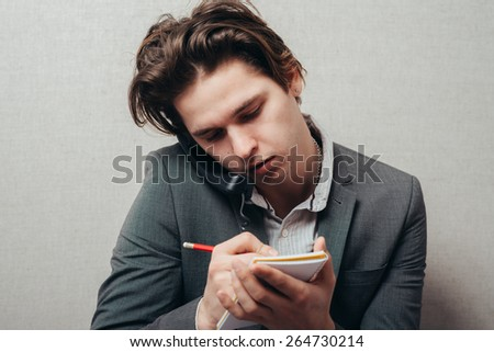 Concentrated on work. Confident young man talking on the landline telephone and writing something in note