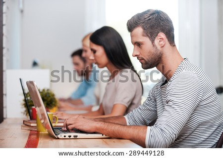 Concentrated on work. Group of confident business people in smart casual wear working at their laptops while sitting in a row at their working places - stock photo