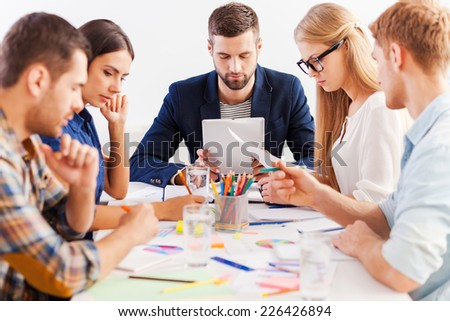 Concentrated on work. Group of confident business people in smart casual wear working together while sitting at the table - stock photo