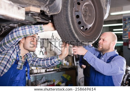 Concentrated professional  mechanics repairing car of client - stock photo