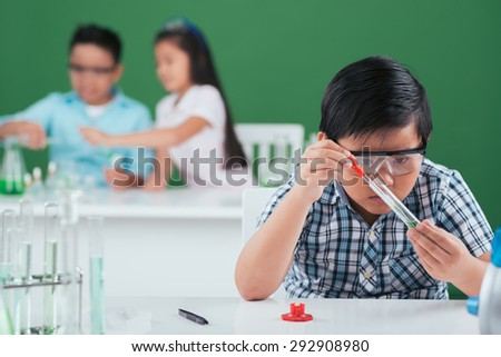 Concentrated pupil performing experiment in the chemistry class - stock photo