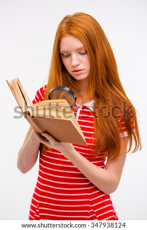 Concentrated redhead pretty young female in red striped top reading book using magnifier glass  - stock photo