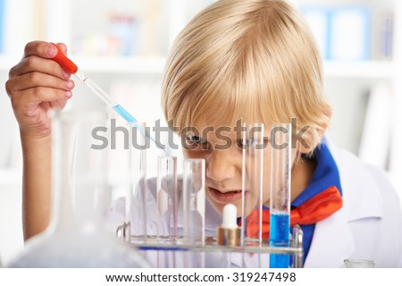 Concentrated schoolchild filling test-tubes with blue liquid