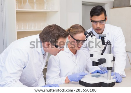 Concentrated scientists working together with microscope in laboratory - stock photo