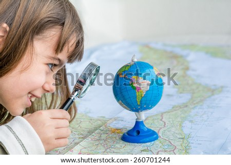 Concentrated seven year old girl examining globe with a magnifying glass - stock photo
