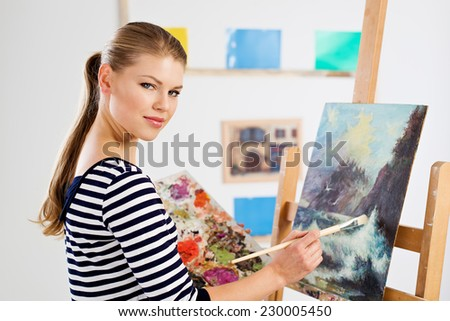 Concentrated student painter standing with color palette and brush at wooden easel. Young artist girl drawing picture in university studio.   - stock photo