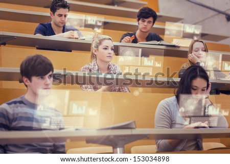 Concentrated students in lecture hall working on their futuristic tablet during lesson - stock photo
