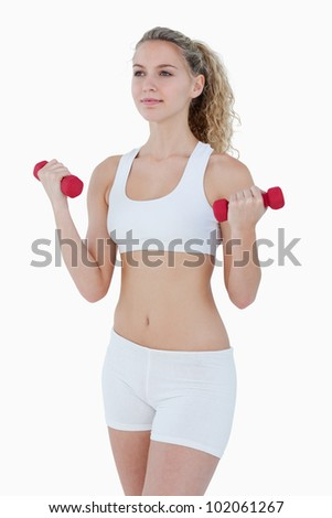 Concentrated teenager lifting red weights against a white background