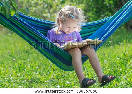 Concentrated two years old girl reading opened book on hanging hammock in green summer garden outdoors - stock photo