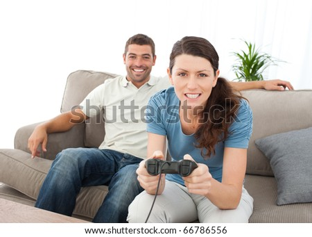 Concentrated woman playing video game with her boyfriend at home - stock photo