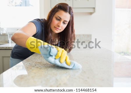 Concentrated woman scrubbing the bar in kitchen - stock photo