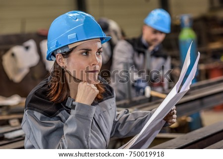 Concentrated woman worker on a industrial dimensioned drawing