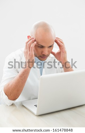 Concentrated worried casual young man using laptop at desk against white background