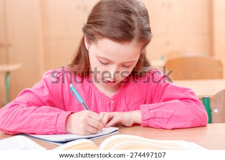 Concentrated writing. Little girl writing at desk in her copy during classes