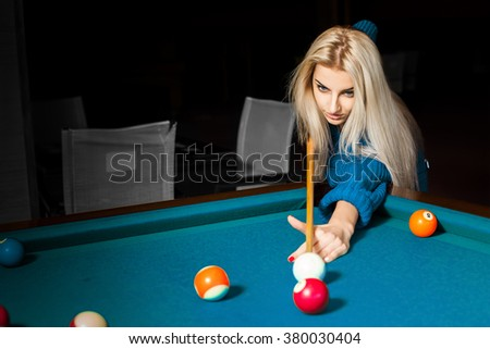 Concentrated young blonde billiard player in game process. Billiard sport concept. American pool billiard. Pool billiard game. - stock photo