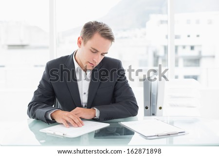 Concentrated young businessman reading documents at office desk - stock photo