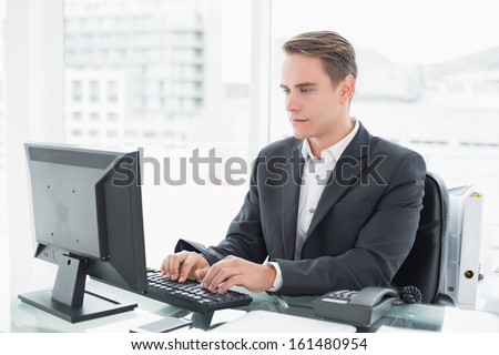 Concentrated young businessman using computer at office desk - stock photo